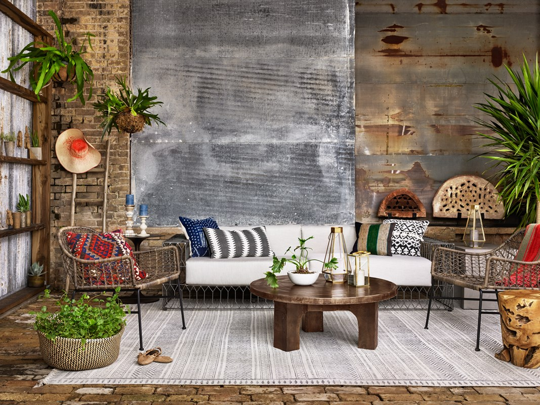 From Left to Right: Bandera Outdoor Woven Club Chair, Tulip Side Table, Torrance Sofa, Cruz Coffee Table, Flatweave Rug, Teak Stool.