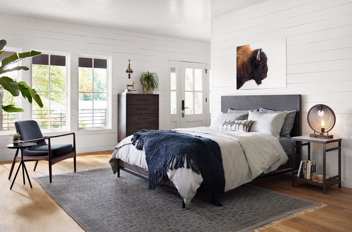 From Left to Right: Corin End Table, Braden Chair, Tribal Block Print Blue Slate Rug, Greta 5 Drawer Dresser, Greta Queen Bed, American Bison, Elliott Nightstand, Rowan Table Lamp.